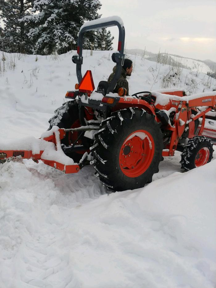 Driving Kubota tractor to plow snow