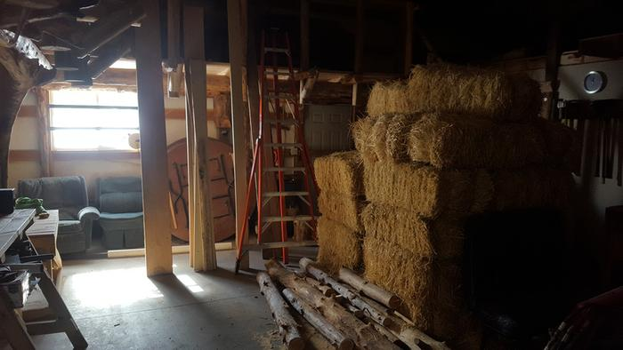 Straw bales stored temporarily in the Auditorium, to be used for insulation and cob projects