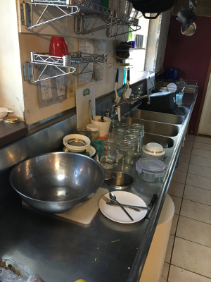 The sink counter with the rest of the dirty dishes
