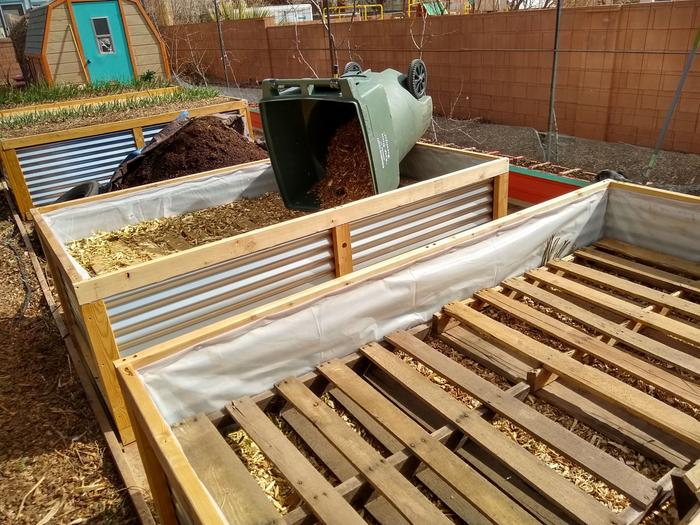 backfilling raised beds with wood chips on top of pallets.