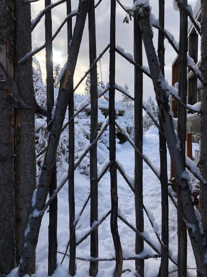wooden, woven gate covered in snow