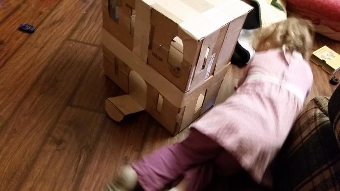 child playing with DIY doll house castle cardboard not finished