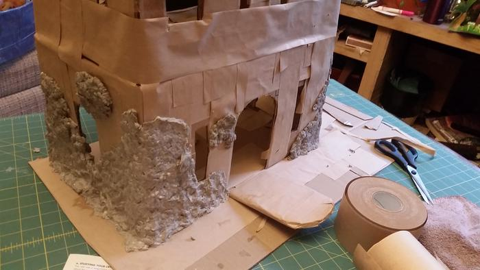 applying paper mache clay cladding to the cardboard castle dollhouse