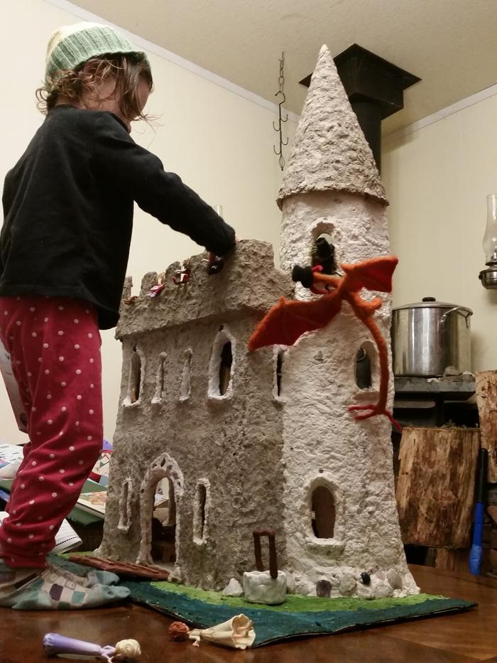 child playing with cardboard castle, dragons, dolls