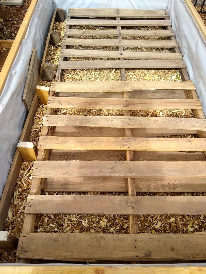 A layer of fresh wood chips, then two pallets on top (one has to be cut down to fit).