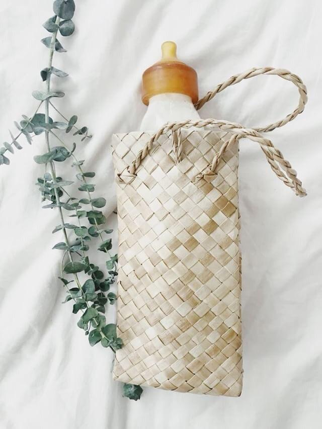 glass baby bottle in woven holder