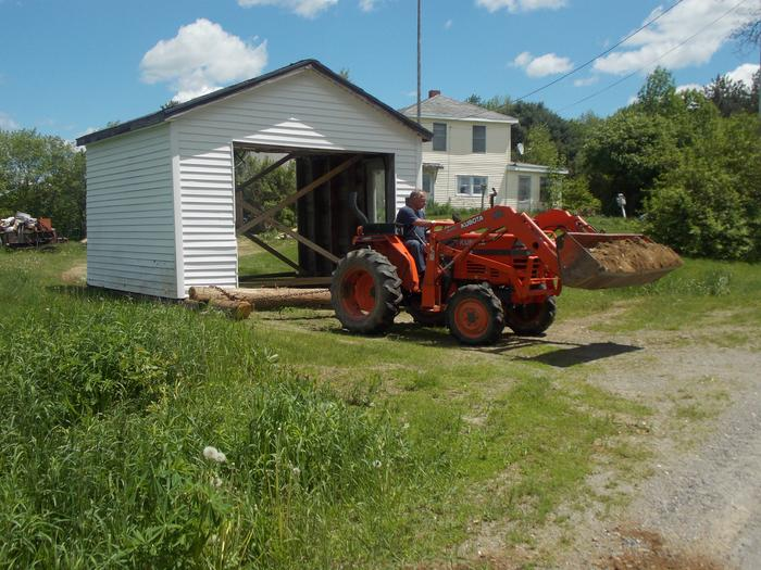 moving building with skids and a subcompact tractor