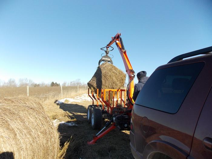 Wallenstein Trailer picking up hay bale