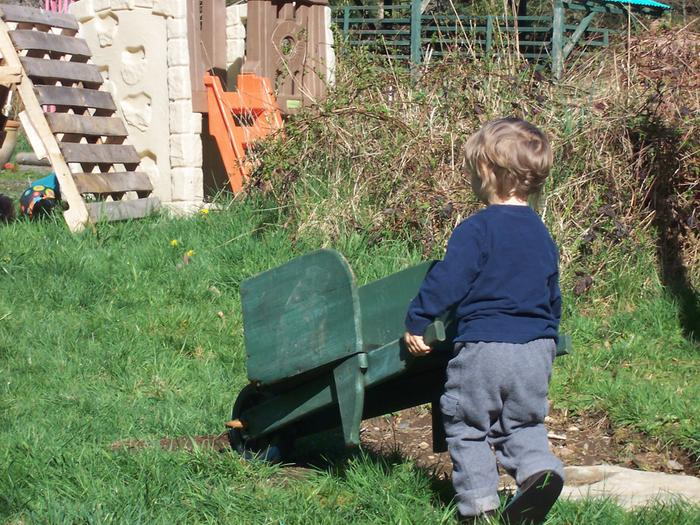 toddler pushing wheelbarrow