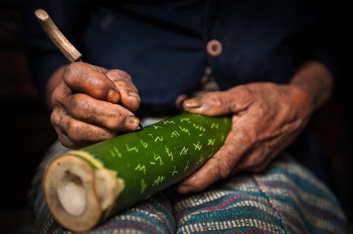 Hanunóo woman named Nais, writing Hanunóo script on a fresh piece of bamboo, Philippines