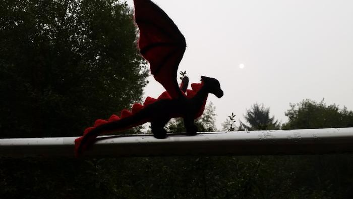 needle-felted black and red dragon in the apocalyptic fire-obscured sun
