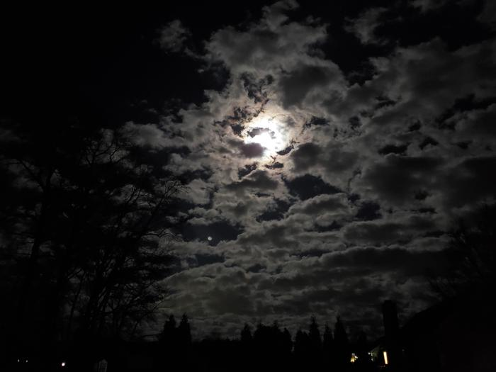 The moon hiding behind the clouds