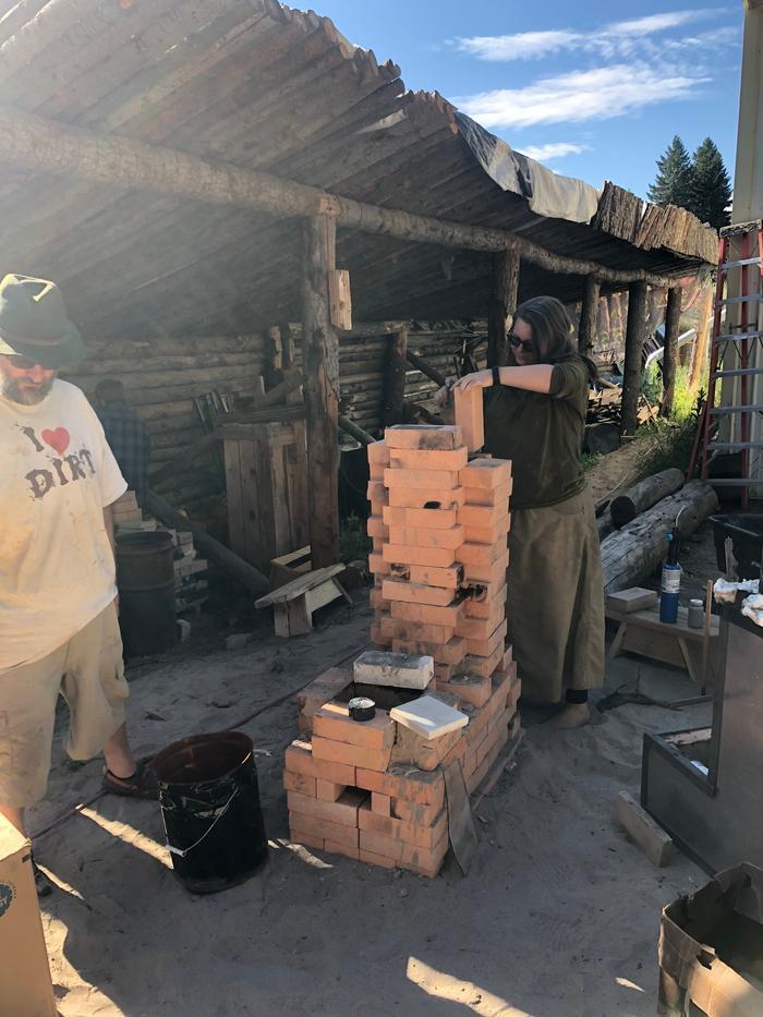 woman building rocket stove with bricks at wheaton labs